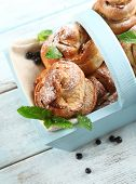Tasty buns with berries in wooden basket on table close-up