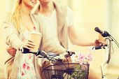 summer holidays, bikes, love, relationship and dating concept - closeup of couple holding coffee and