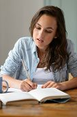 Teenage girl studying book at home writing notes concentrating