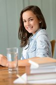 Smiling teenage girl student at home books side view