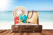 Concept of summer traveling with old suitcase and accessories. Blur beach on background