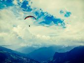 Vintage retro effect filtered hipster style travel image of freedom flight concept - paraplane in sky above Himalayas mountains