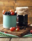Ripe blackcurrants and gooseberries in mug and glass jar with tasty jam on board, on wooden backgrou