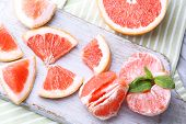 Ripe grapefruits on cutting board, on wooden table, on light background