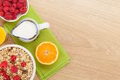 Healty breakfast with muesli, berries and orange juice. View from above on wooden table with copy sp