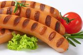 detail of grilled hot dog sausages with vegetable garnish