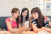 Asian lady in the restaurant and share something in mobile phone with her friends.