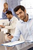 Portrait of handsome young businessman sitting in office, using mobilephone, looking at camera.