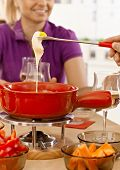 Closeup photo of cheese fondue with melting cheese.