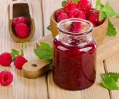 Glass Jar Of Jam With Fresh Raspberries