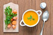 pic of spooning  - Carrot soup close up with fresh carrot parsley spoon and salt shaker - JPG
