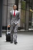 Portrait of happy young businessman walking with wheeled suitcase