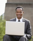 Portrait of a happy African American businessman using laptop