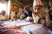 KATHMANDU, NEPAL - DEC 9, 2013: Unknown children doing homework at Jagadguru School. School establis