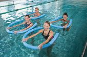 Fitness class doing aqua aerobics with foam rollers in swimming pool at the leisure centre