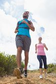 Fit attractive couple jogging down mountain trail on a sunny day