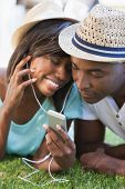 Happy young couple listening to music on the grass on a sunny day