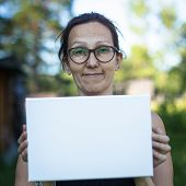 Banner for your message: Woman holding clean white sheet paper, outdoors.