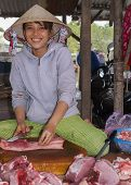 Young Female Butchers Sits In The Middle Of Fresh Cut Pieces Of Meat.
