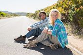 Attractive couple sitting on the road on a sunny day