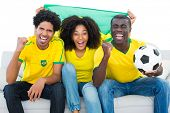 Excited football fans in yellow sitting on couch with brazil flag on white background