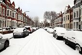 stock photo of slippery-roads  - Snow cityscape of a terraced street in London England with slippery blizzard conditions showing cars covered with ice and a blanket of snow - JPG