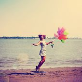 a pretty woman enjoying summer outside with a bunch of balloons toned with a retro vintage instagram