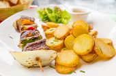 tasty grilled meat and vegetables skewers on a slate plate