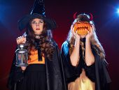 stock photo of antichrist  - Portrait of two females with lantern and pumpkin posing for camera - JPG