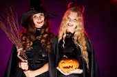 stock photo of antichrist  - Portrait of two happy females with broom and pumpkin looking at camera with smiles - JPG