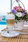Latte In A Glass With A Blurred Background Of A Beautiful Bouquet Of Flowers
