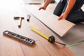 stock photo of cut  - Man installing new laminated wooden floor - JPG