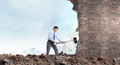 Young determined businessman with big hammer in hands crashing wall