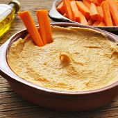 closeup of an earthenware bowl with appetizing hummus on a rustic wooden table