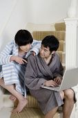 Young couple in bathrobe sitting on stairway with laptop