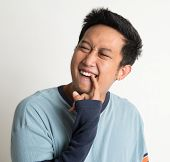 Nasty Asian man portrait, something stuck in his teeth,  digging by hand, on plain background