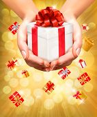 Holiday background with hands holding gift boxes. Concept of giving presents.