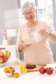 Portrait of elderly lady preparing healthy breakfast with cereal, orange juice and fruits.