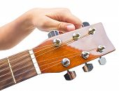 stock photo of fret  - Hand tuning a guitar from headstock isolated on white background.