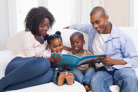 stock photo of couch  - Happy family on the couch reading storybook at home in the living room - JPG