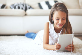 stock photo of pre-teens  - Pre teen girl playing on tablet pc laying down on a white carpet at home - JPG