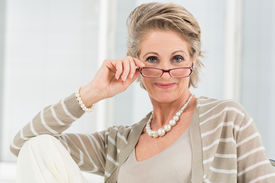 foto of maturity  - Portrait Of Happy Mature Woman Looking Through Glasses - JPG