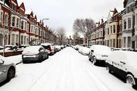 picture of slippery-roads  - Snow cityscape of a terraced street in London England with slippery blizzard conditions showing cars covered with ice and a blanket of snow - JPG