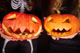 stock photo of antichrist  - Photo of carved Halloween pumpkins on female palms - JPG