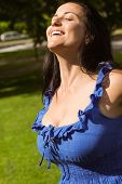 Pretty brunette in blue dress enjoying the sunshine in the park