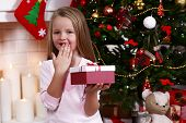Little girl holding present box near Christmas tree on fireplace with candles background
