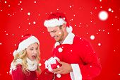 Young festive couple against red background