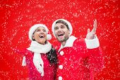 Festive young couple against red background