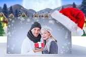 happy winter couple with gift against quaint town with bright moon