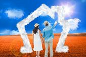 Happy hipster couple holding hands and looking against sunny brown landscape